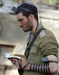 Lieut.-Asael-Lubotzky-prays-with-tfillin-after-the-Battle-of-Bint-Jbeil-during-the-2006-Lebanon-War-photo-by-Yoav-Lemmer-via-Wikimedia-Commons-1